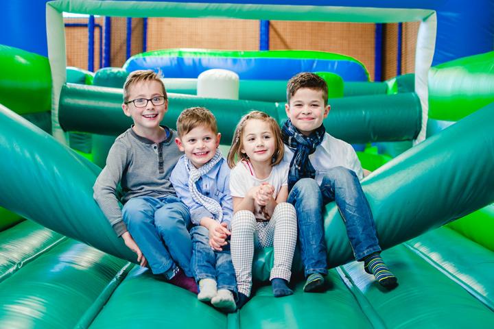 Vier kinder sitzen nebeneinander in der Hüpfburg