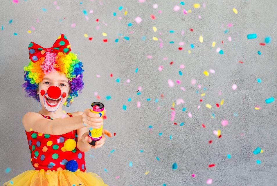 Kind als Clown verkleidet mit Konfetti